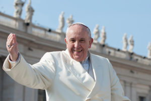 Pope Francis with a raised arm outside a building