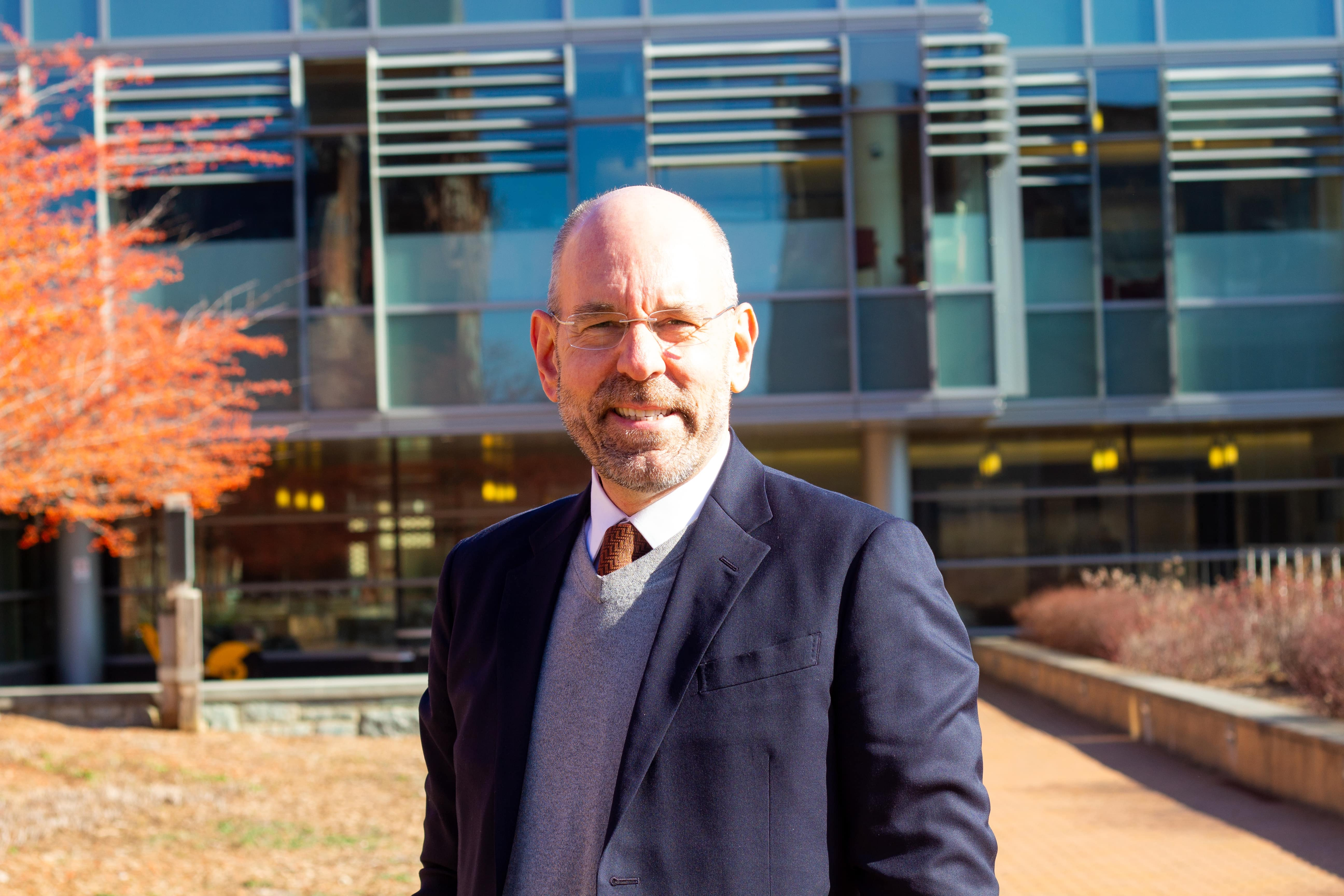 Professor Brandes stands in front of the Regents Building smiling