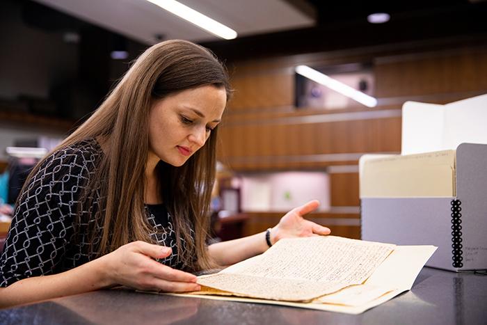 Cassandra Berman sits at a desk looks through a manuscript from the 1800s
