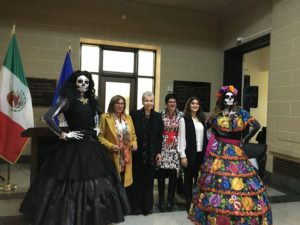 Yamel Sarquis standing with five other women, two of whom are dressed in Day of the Dead masks and costumes.