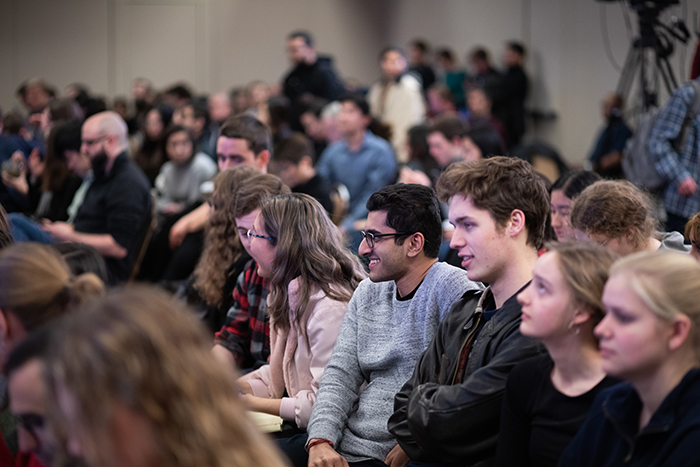An audience of mostly students sits and stands in a packed room