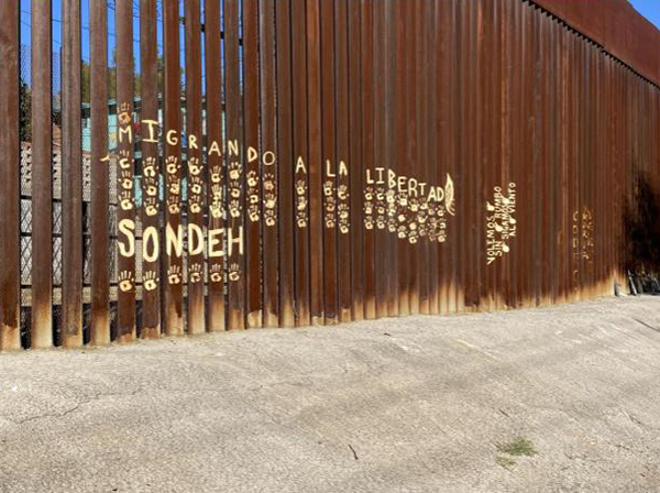 The wall at the border of the United States and Mexico with the Spanish words for migrating to freedom