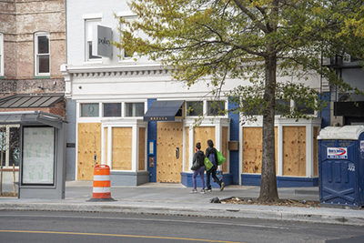 Two people walk by a boarded up restaurant