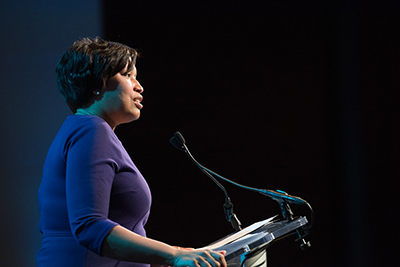 Mayor Muriel Bowser at a podium speaking into a microphone