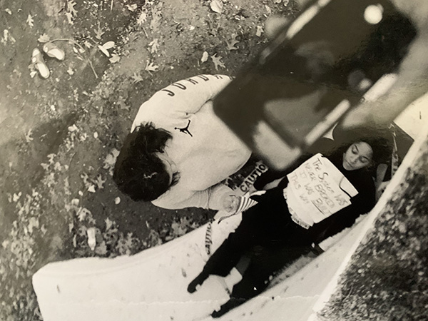 """Photo of a hand taking an iPhone photo of a woman lying down wearing a sign on her chest reading """"The System Was Never Broken It was BUILT this way"""" and another woman crouched over her."""