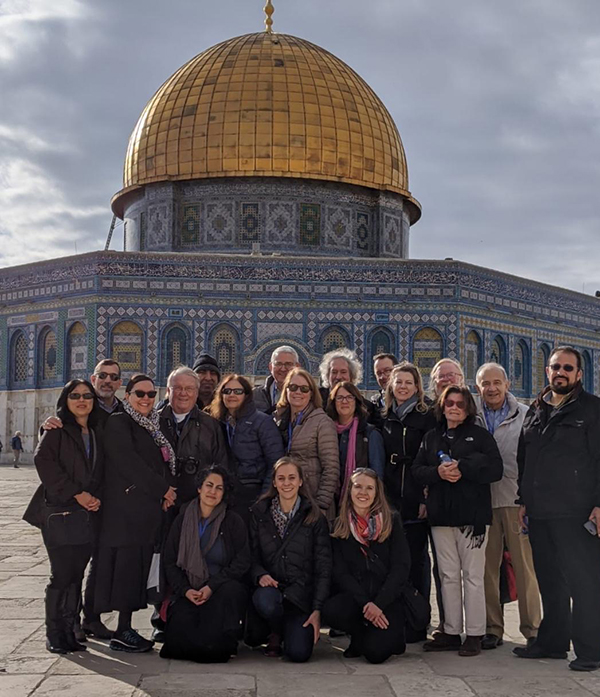 A group of men and women in front of the Dome of the Rock